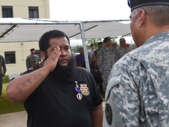 Spc. John Chargualaf II salutes Brig. Gen. Roderick Leon Guerrero after being awarded the Purple Heart during the Guam National Guard Retreat Ceremony at the National Guard Readiness Center in Barrigada on Aug. 7.