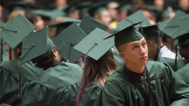 A graduate waits to cross the stage at the Moby Center during the Fossil Ridge High School graduation ceremony Friday, May 22, 2015.
