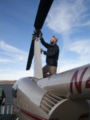 Matt Kinkade, a student at the Upper Limit Aviation conducts a post flight check on a helicopter on Monday January 27, 2014.
