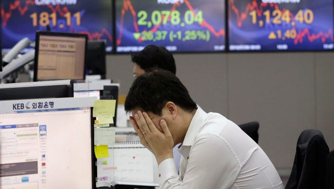 A currency trader covers his face with his hands at the foreign exchange dealing room of the Korea Exchange Bank headquarters in Seoul, South Korea, Monday, July 6, 2015. Asian markets mostly fell Monday as investors reacted to Greece's sound rejection of terms set by its international creditors, deepening uncertainties over its status as a member of the 19-nation eurozone. (AP Photo/Ahn Young-joon) ORG XMIT: SEL103