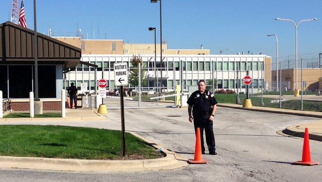 A security guard stands in front of the air-traffic control center in Aurora, Ill., on Sept. 26, 2014, after all flights in and out of Chicago's two airports were halted following a fire at the facility.