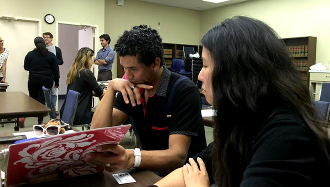 Adrian Valenzuela, 22, (left) and his mother, Patricia, 47, listen as Legal Aid attorneys discuss strategies for students affected by the sudden shutdown of ITT Technical Institute on Sept. 8 during a workshop conducted by Legal Aid Foundation of Los Angeles for ITT students to explain their options. About 20 students attended the meeting. Valenzuela completed a two-year program in electrical engineering this summer but never received a diploma.