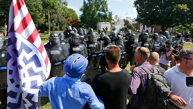 White nationalist demonstrators hold their ground against Virginia State Police as police fire tear gas rounds in Lee Park in Charlottesville, Va., Saturday, Aug. 12, 2017.  Gov. Terry McAuliffe declared a state of emergency and police dressed in riot gear ordered people to disperse after chaotic violent clashes between white nationalists and counter protestors. (AP Photo/Steve Helber)