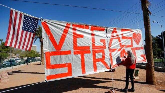 """In this Oct. 5, 2017, file photo, Las Vegas resident Nancy Cooley signs a Vegas Strong banner honoring the victims of a mass shooting in Las Vegas. The official slogan of Las Vegas, """"What happens here, stays here,"""" is back by popular demand. The destination's tourism agency revived the 15-year-old slogan this week, three months after it was put on hold following the October mass shooting."""