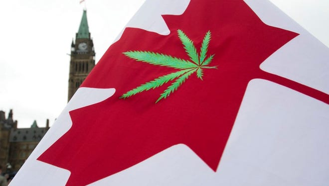 In this April 20, 2015 file photo, a Canadian flag with a cannabis leaf flies on Parliament Hill during a 4/20 protest in Ottawa, Ontario. Canada is following the lead of Uruguay in allowing a nationwide, legal marijuana market, although each Canadian province is working up its own rules for pot sales.