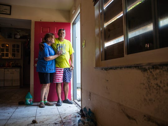 Lori and Rodney Malone stand in the front doorway of their home in Bonita Springs on Tuesday September 26, 2017. The couple was finally able to begin clearing out the interior of their house this week, which is now riddled with mold, after several feet of standing water from Hurricane Irma flooded the neighborhood.