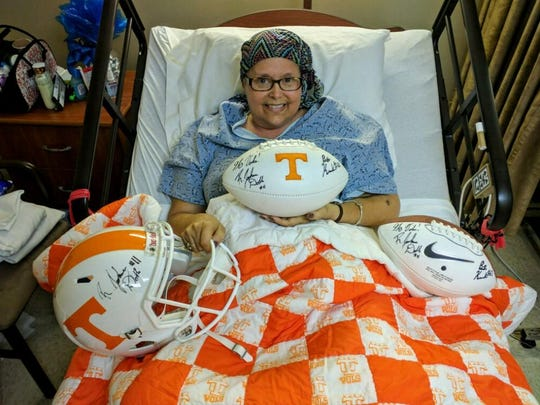 Jackie Kelly received autographed footballs and a helmet from Tennessee quarterback Joshua Dobbs and offensive lineman Brett Kendrick during their visit as she battles cancer.