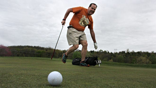 Speed golfer Joel Alexander drops his clubs while running to line up a putt at Rivercut Golf Course.