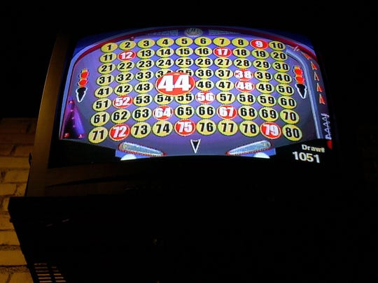 A TV screen above a bar shows Keno drawing numbers.