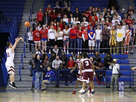 St. Elizabeth's Nathan Thomas makes a three-pointer in front of the Caravel student section in the first half of a DIAA state tournament semifinal at the Bob Carpenter Center Thursday.