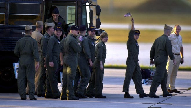 In this April 2001 file photo, a U.S. crew arrives in good health, good spirits: As one crew member waves an American flag, fellow spy plane crew members who had been detained on China's Hainan island since April 1 prepare to board a military transport plane at Andersen Air Force Base.