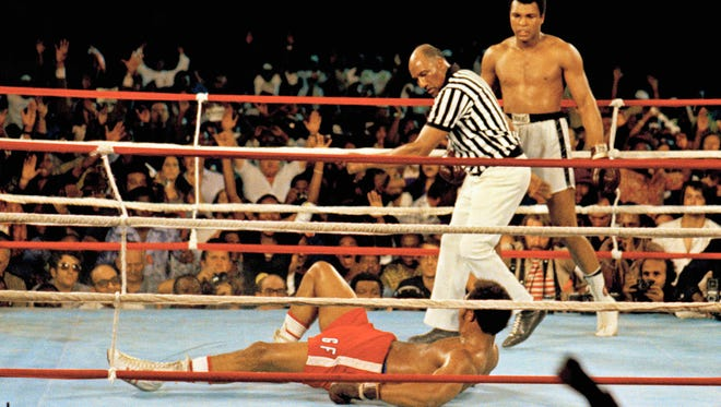 Muhammad Ali (right) stands back as referee Zack Clayton calls the count over opponent George Foreman in Kinshasa, Zaire, on Oct. 30, 1974. Ali won the fight by a knockout in the eighth round.