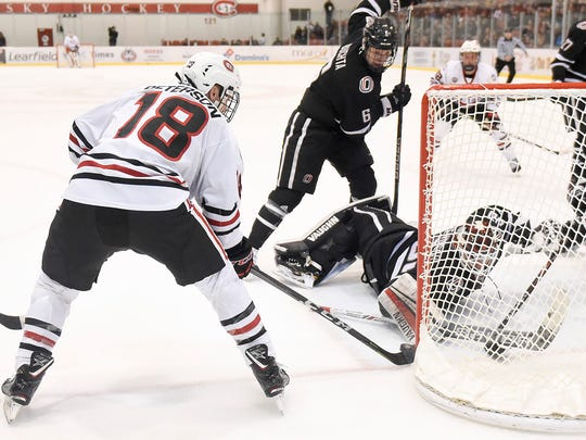 St. Cloud State's Judd Peterson tries to slip the puck between the post and Nebraska-Omaha goalie Evan Weningercduring the first period Saturday, Feb. 3, at the Herb Brooks National Hockey Center.