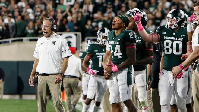 While the Spartans celebrate the final seconds of MSU's win over Indiana Saturday, Oct. 21, 2017, Coach Mark Dantonio stays focused until the end.