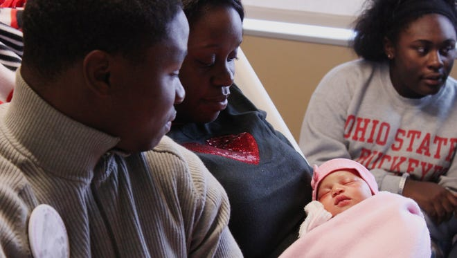 Ricky Herron and Tierra Burks sit with their child, Madilynn Nichole Herron, at Jackson-Madison County General Hospital Thursday. Madilynn is the first baby of 2015 in Jackson.