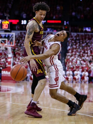 Wisconsin's D'Mitrik Trice, right, runs into Minnesota's Amir Coffey (5) during the first half of an NCAA college basketball game Sunday, March 5, in Madison, Wis.