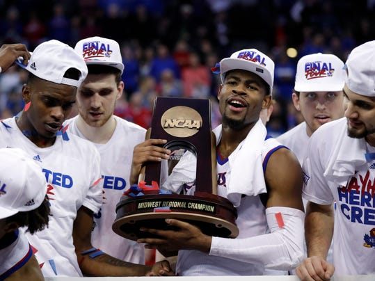 Kansas' Malik Newman holds the trophy after defeating Duke in a regional final game in the NCAA men's college basketball tournament Sunday, March 25, 2018, in Omaha, Neb. Kansas won 85-81 in overtime. (AP Photo/Charlie Neibergall)