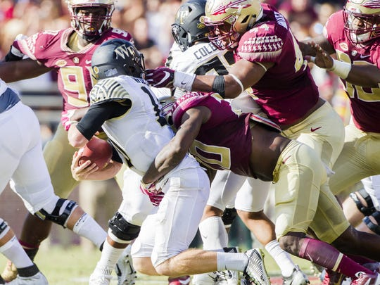 Florida State defenders Trey Marshall, bottom, and DeMarcus Walker sack Wake Forest quarterback John Wolford in the first half of an NCAA college football game in Tallahassee, Fla., Saturday, Oct. 15, 2016. Florida State defeated Wake Forest 17-6. (AP Photo/Mark Wallheiser)