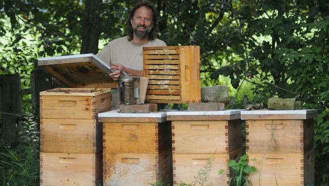 Bill Beebe of Beebe's Bees with one of his beehives Saturday afternoon.