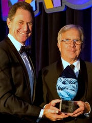 Dan Collins, right, Corning Inc. vice president of corporate communications, accepts Corning's award from Ken Solomon,  BCA Executive Board member for Americans for the Arts.