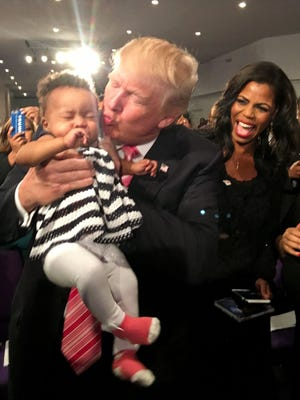 Donald Trump does the standard presidential dance, kissing a baby at Greater Faith Ministries International in Detroit on Sept. 3, 2016 as Omarosa, is campaign's director of African-American outreach, looks on.