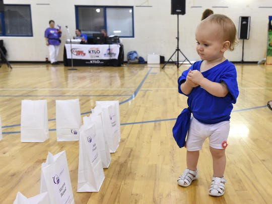 Kinsley Tuberville, 15 months, checks out luminarias.