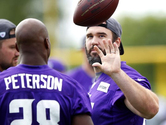 Minnesota Vikings center John Sullivan (65) catches the ball tossed by running back Adrian Peterson (28) during the first day of training camp Friday at Minnesota State University in Mankato.