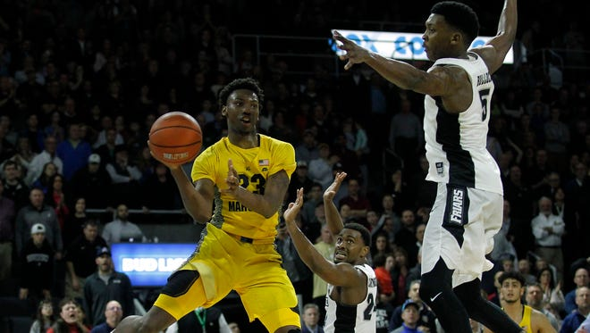 Marquette guard JaJuan Johnson passes the ball as Providence forward Rodney Bullock defends.