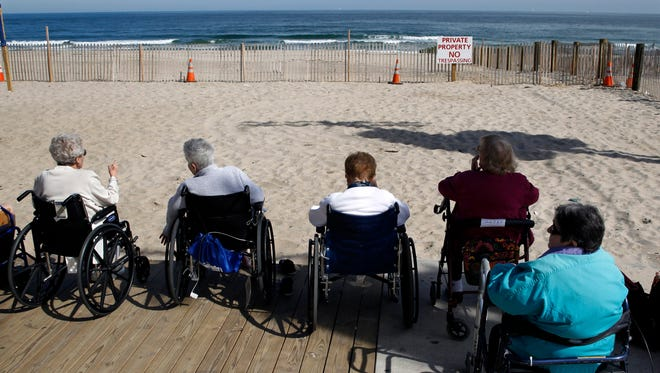 Elderly people from a nearby senior citizen facility sit on the edge of the boardwalk and look out over the ocean on the first day of Fall Tuesday, Sept. 23, 2014, in Seaside Park, N.J.