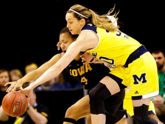 Iowa Hawkeyes forward Chase Coley (4) fends off a steal attempt by Michigan Wolverines center Hallie Thome (30) during the Women's Big 10 Basketball Championship at Bankers Life Fieldhouse in Indianapolis on March 2, 2016.