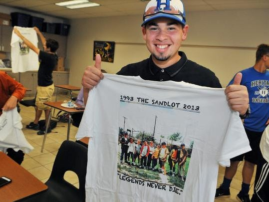 "Vadiel Vazquez, catcher with the Heritage High baseball team, shows off his Sandlot t-shirt given to him by David Evans, of New Smyrna Beach, writer, director and narrator of ""The Sandlot,"" signed autographs for the Heritage High Baseball team before their 14th game Monday afternoon. Evans paid a surprise visit to the team after hearing about their wager with their coach; if they win all 14 of their games, they could name his baby. The team came up with the name Benjamin Smalls, from a character in the movie The Sandlot."""