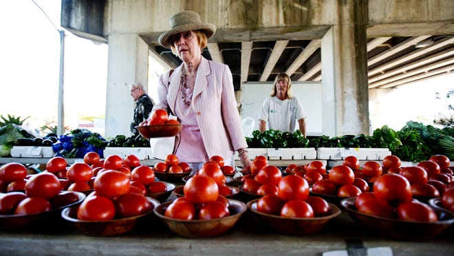 Diane McGee, a resident of Fort Myers, picks out a bowl of tomatoes at Horace Brittain's stand at the farmers market in downtown Fort Myers.