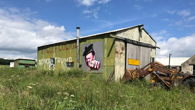A farm shed on Sheila and Michael Forbes' property near Aberdeen, Scotland, with a mural and words that say 'Trump lies.'