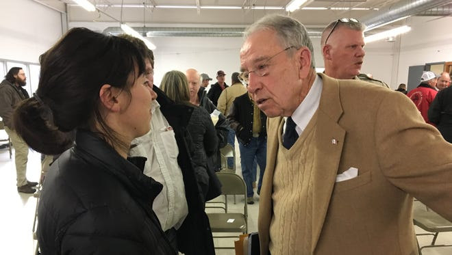 U.S. Sen. Chuck Grassley, R-Ia., speaks with a woman after a town hall meeting in Bloomfield, Ia.