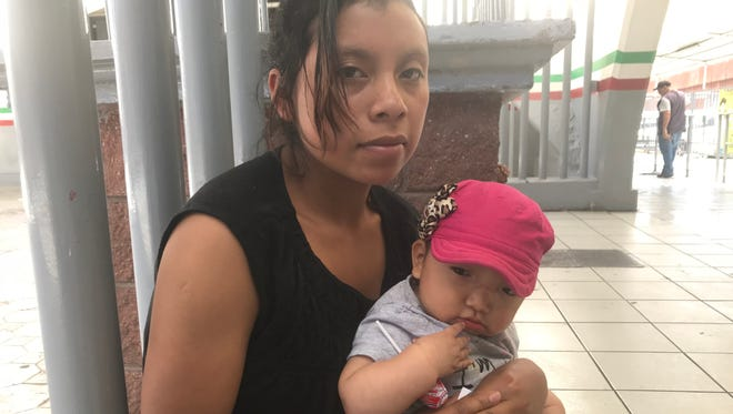 Manuela Rodriguez Garcia holds her daughter, seven-month-old Ashley, as she waits her turn to talk to an immigration officer to seek asylum in the U.S. at the DeConcini port of entry in Nogales on May 24, 2018.