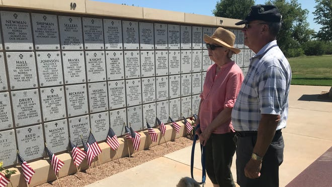 Kathy and Bill Arno, of Abilene, view the names and inscriptions of veterans who appear on one of the walls at a memorial at Texas State Veterans Cemetery at Abilene on Memorial Day. Their dog, Millie, joined them.