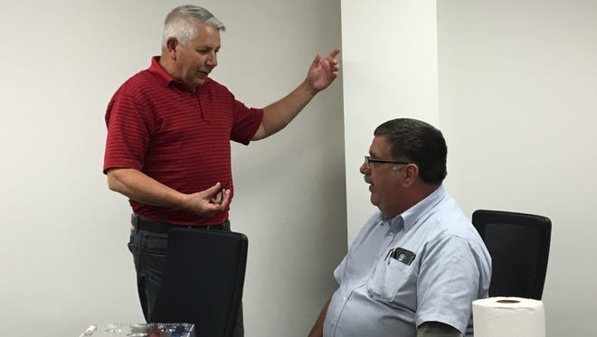 Mansfield building and codes manager J.R. Rice, left, talks with Richland County Land Bank board member and Madison Township trustee Tom Craft after a land bank meeting Wednesday, June 27, 2018. The land bank recognized Rice's contributions to the land bank ahead of his retirement from the city.