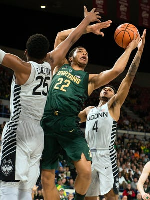 Nov 24, 2017; Portland, OR, USA; Michigan State Spartans guard Miles Bridges (22) drives to the basket against Connecticut Huskies forward Josh Carlton (25) and guard Jalen Adams (4) during the first half during the Phil Knight Invitational tournament on Friday, Nov. 24, 2017, in Portland, Ore.