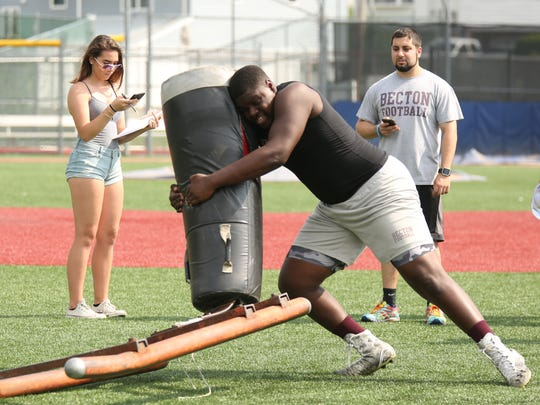 Becton Offensive Lineman Greg Anderson tackles the dummy as his the counter keeps a close eye on time remaining during The South Bergen 7 on 7 Football and Linemens' Challenge held at Wallington High School (pictured)  and  Becton High School.