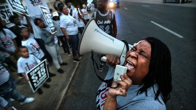 Dunetra Merritt chants with fellow protesters outside the McDonald's on Poplar during a protest for higher wages for fast food workers. Dozens of workers and their children voiced their support of a $15 wage.