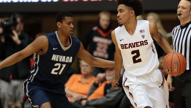 Nevada Wolf Pack guard Eric Cooper Jr (21) defends as Oregon State Beavers guard Stephen Thompson Jr. (2) dribbles the ball at Gill Coliseum.