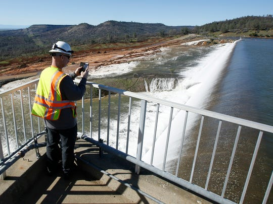 Jason Newton of the Department of Water Resources takes a picture of water going over the emergency spillway at Oroville Dam on Saturday. Water started flowing over the emergency spillway at the nation's tallest dam for the first time Saturday after erosion damaged the Northern California dam's main spillway.