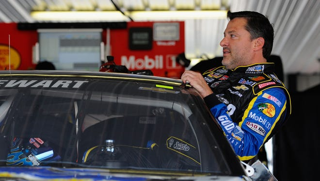 Tony Stewart, driver of the #14 Code 3 / Mobil 1 Chevrolet, gets into his car in the garage during Practice for the NASCAR Sprint Cup Series GoBowling.com 400 at Pocono Raceway on August 1, 2014 in Long Pond, Penn..