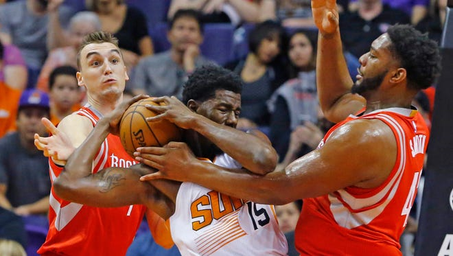Phoenix Suns center Henry Sims (15) fights for the basketball with Houston Rockets forward Sam Dekker (left) and Joshua Smith during the first half of their NBA preseason game on Tuesday, Oct. 13, 2015 in Phoenix.