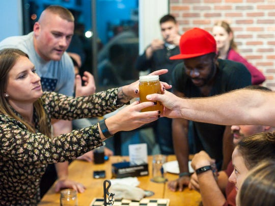 Customers grab a pint of beer at the 1st Republic Brewing Company taproom in Essex on Friday, November 3, 2017.