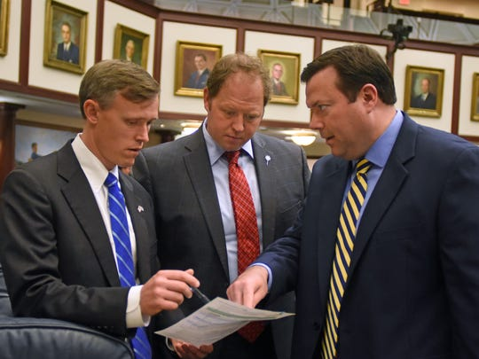 State Reps. Frank White, R-Pensacola, Jayer Williamson, R-Pace, and Clay Ingram, R-Pensacola, confer on the floor of the House of Representatives in Tallahassee.