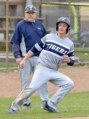 Twinsburg junior Nick Bonnizzio pauses at third base in front of Tigers coach Jeff Luca during a game earlier last season.