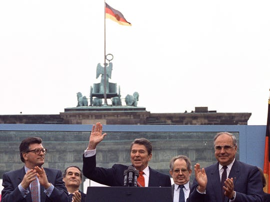 """In this June 12, 1987, photo, U.S. President Ronald Reagan acknowledges the crowd after his speech in front of the Brandenburg Gate in West Berlin, in which he said, """"Mr. Gorbachev, tear down this wall!"""""""