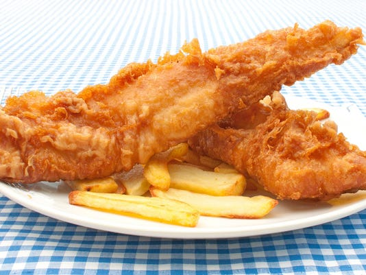 Plate of battered fish and chips on a blue checkered table