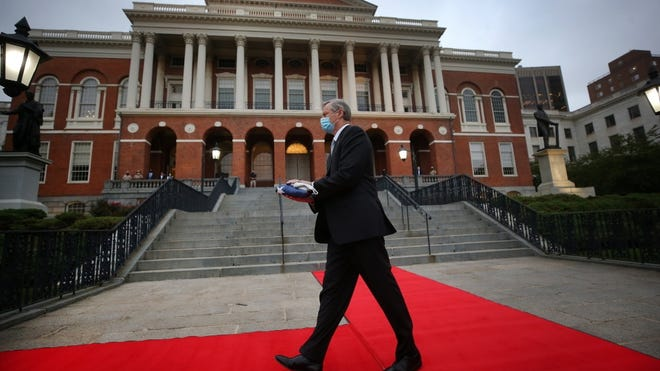 Gov. Charlie Baker walks down the State House steps Friday morning carrying an American flag to remember Sept. 11, 2001 at an annual flag-raising ceremony, absent the many others who normally attend.